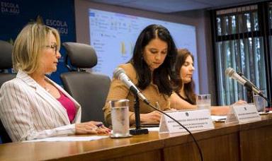 Foto com três mulheres sentadas. Em uma mesa elas apoiam seus braços. Em cima da mesa há 2 microfones, três copos com água e 2 prismas de identificação de palestrantes. Ao fundo há uma tela de projeção.