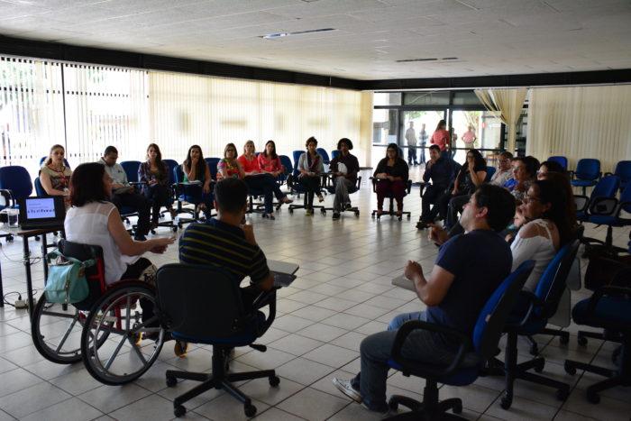Foto com 25 pessoas sentadas em uma roda na Sala de Convivência da Enap. Há uma pessoa em pé, na porta, e 4 pessoas na área externa.