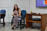 Foto da mediadora da roda, Anna Paula Feminella, em cadeira de rodas, ao lado de uma mesa. Ao fundo há uma tela de projeção.