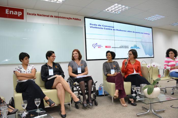 Foto de 6 mulheres sentadas, lado a lado. Ao fundo, em destaque, a logo da Enap e tela com o assunto da roda.