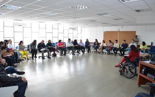Foto de uma sala de aula com 24 pessoas (12 homens e 12 mulheres) sentadas em formato U, voltadas para a frente, onde há uma pessoa em cadeira de rodas. Ao fundo, uma parede formada com janelas de vidro refletindo a claridade do dia. Na outra parede, uma pessoa em pé e um quadro de cortiça.