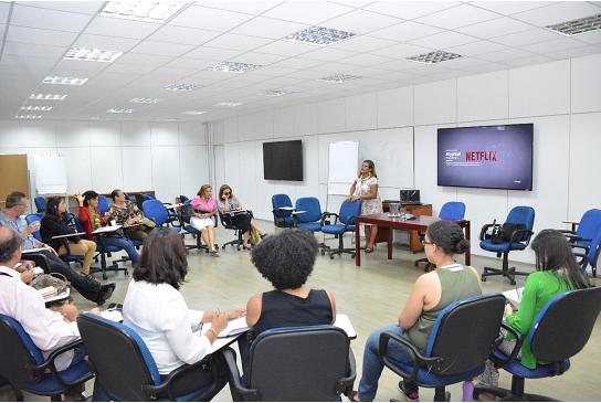 Foto da sala com pessoas sentadas em círculo. Ao centro da imagem, em pé, a estagiária Maria Morais, uma das mediadoras da atividade.
