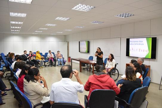 Foto de uma sala de aula com 22 pessoas dispostas em formato U. Uma delas é uma bebê, e há 13 mulheres e 8 homens.