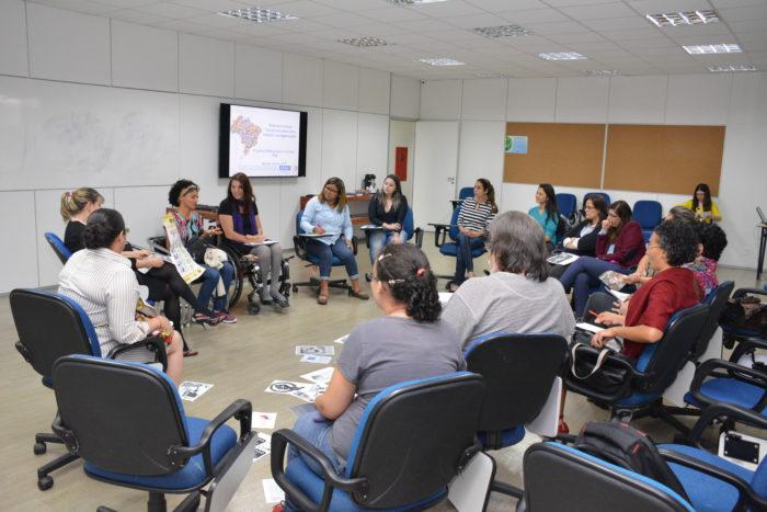 Foto de uma sala de aula com 16 pessoas sentadas em círculo. Há papéis com gravuras no chão. Ao fundo, uma tela de projeção com slide de apresentação do Programa Senai de Ações Inclusivas.