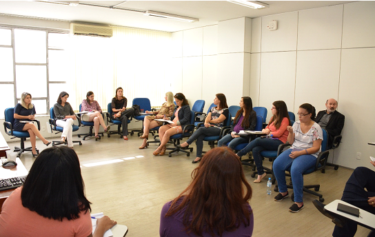 Foto com 14 pessoas sentadas em uma sala de aula