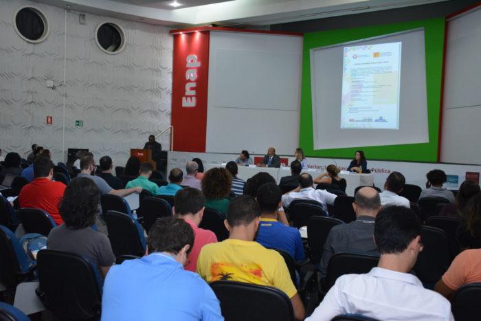 Foto de evento no auditório da Enap, com imagem das costas de pessoas sentadas em cadeiras em fila viradas para frente onde estão quatro pessoas em uma mesa e um homem em pé. Atrás deles o telão e o logotipo da Enap em destaque.